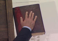 A still image taken from video shows Syria's President Bashar al-Assad's hand on the Koran as he is sworn in for a new seven-year term at the presidential palace in Damascus July 16, 2014. REUTERS/Syria TV via Reuters TV