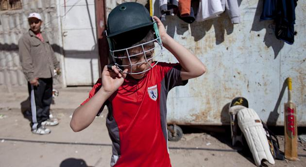 Caacupe cricket team Maxi Rubin puts on his helmet during a training session at the Villa 21-24 slum in Buenos Aires, Argentina, Saturday, March 22, 2014. The International Cricket Council has recogni