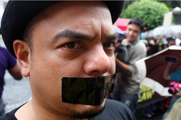 Popular tourist guide and culture activist Carlos Celdran, with a black tape on his mouth, joins private citizens and different militant groups in a protest rally against the new Anti-Cybercrime Law by the Aquino government, at the Supreme Court in Manila, on 02 October 2012. The Supreme Court is set to tackle during its en banc session today several petitions questioning the constitutionality of certain provisions of Republic Act (RA) 10175, or the Cybercrime Prevention Act of 2012. Protesters called the law as a threat to Filipinos' right to freedom of expression. (Jhun Dantes Jr/NPPA Images)
