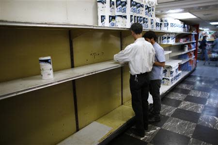 Supermarket staff work next to partially empty shelves of toilet paper in Caracas May 16, 2013. REUTERS/Jorge Silva