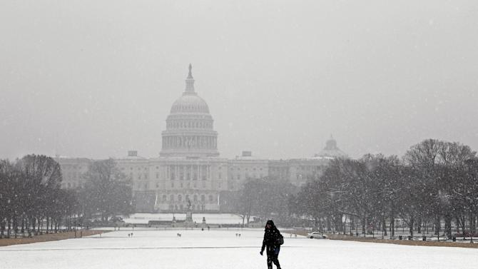 With the Capitol in the background, a person walks through the fallen snow across the National Mall in Washington, Monday March, 25, 2013. A wide-ranging storm hit the East Coast after blanketing the Midwest and burying thoughts of springtime weather under a blanket of heavy wet snow and slush, though less snow was predicted to fall as the storm moved eastward. (AP Photo/Jose Luis Magana)