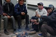 Migrant job seekers sit around a fire to keep warm on a street in Hanoi, on February 6, 2013. From growing numbers of people with depression to families bankrupted by stock market investments, many are suffering in Vietnam's slow-burn economic crisis -- and blame the communist regime for their woes
