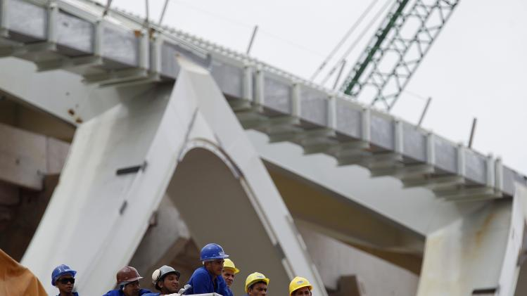 Workers from the Andrade Gutierrez construction company stand on a ledge outside the Arena Amazonia stadium in Manaus
