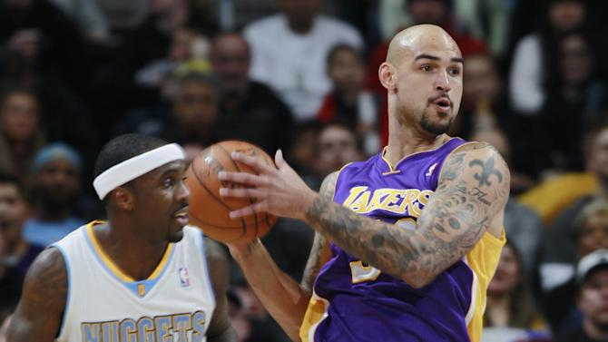 Los Angeles Lakers center Robert Sacre, back, pulls in loose ball in front of Denver Nuggets guard Ty Lawson in the first quarter of an NBA basketball game in Denver on Friday, March 7, 2014