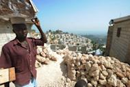 A man walks in a hillside slum in Port-au-Prince, Haiti, on July 12. About 80 percent of people in the capital live below the poverty line, many in squalid tent cities or in rickety housing near the edge of deadly ravines
