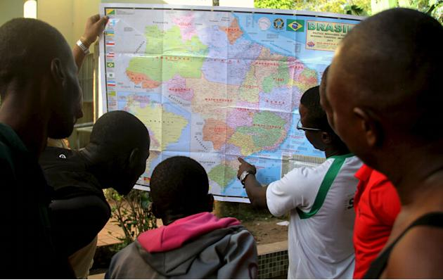 Haitians look at a map of Brazil as they  wait for transport to other Brazilian cities to look for work, at a state government-run refugee camp in Rio Branco