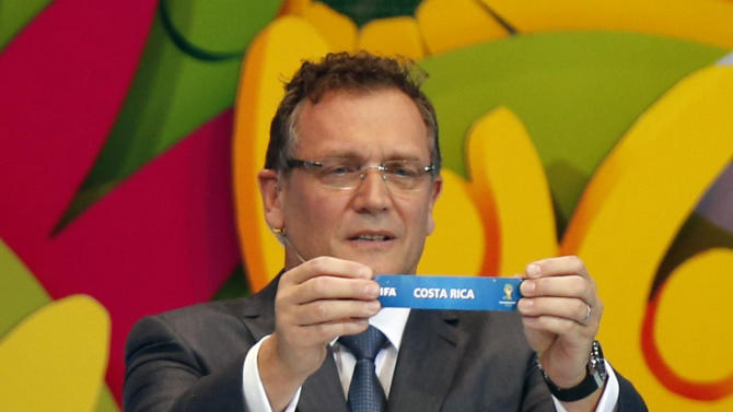"""FIFA Secretary General Jerome Valcke holds the slip showing """"Costa Rica"""" during the draw for the 2014 World Cup at the Costa do Sauipe resort in Sao Joao da Mata"""