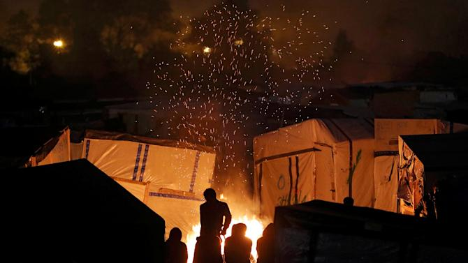 "Sparks fly from a fire as migrants sit near for warmth at the end of the first day of the evacuation and transfer to reception centers of migrants living in the ""Jungle"" in Calais"