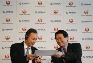 Japan Airlines President Yoshiharu Ueki exchanges documents with Airbus Chief Executive Fabrice Bregier during their joint news conference in Tokyo