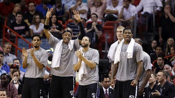 Brooklyn Nets players come off the bench as they celebrate a basket during the second half of an NBA basketball game against the Miami Heat, Wednesday, March 12, 2014 in Miami. The Nets defeated the Heat 96-95