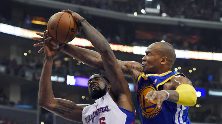 Los Angeles Clippers center DeAndre Jordan, left, puts up a shot as Golden State Warriors forward Marreese Speights defends during the first half in Game 1 of an opening-round NBA basketball playoff series, Saturday, April 19, 2014, in Los Angeles