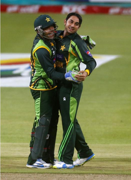 Pakistan's Umar Akmal and Saeed Ajmal celebrate as South Africa's Hashim Amla is dismissed during their second Twenty20 cricket match in Cape Town