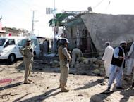 Pakistani security officials examine the site of a suicide bombing in Khar, the main town of Bajaur district, near the Afghan border. A teenage suicide bomber targeted police in a bustling Pakistan town square on Friday, killing at least 24 people and wounding dozens in the tribal area near the Afghan border, officials said
