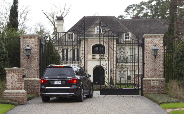 A car enters a gate to the home of NFL running back Adrian Peterson Wednesday, March 4, 2015, near Houston. Minnesota Vikings head coach Mike Zimmer and GM Rick Spielman plan to travel to Peterson&#39