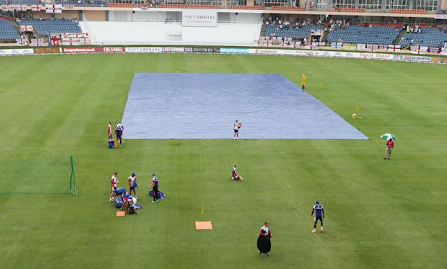 Cricket: The covers go on before the start of play as England players warm up