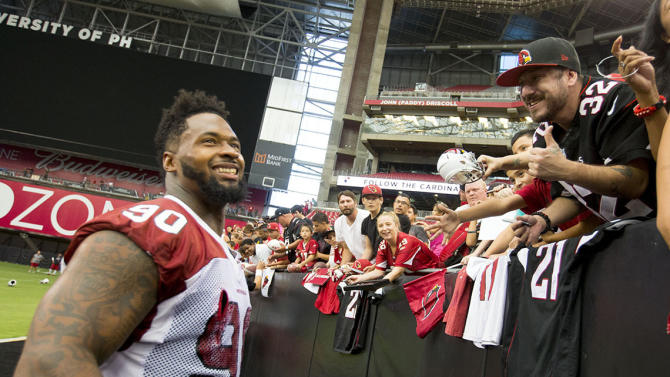 Arizona Cardinals' Darnell Dockett talks with fans during NFL football training camp in Glendale, Ariz., Saturday, July 26, 2014