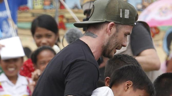 Former England soccer captain Beckham carries a boy as he plays soccer with typhoon survivors at an evacuation centre in Tanauan, Leyte