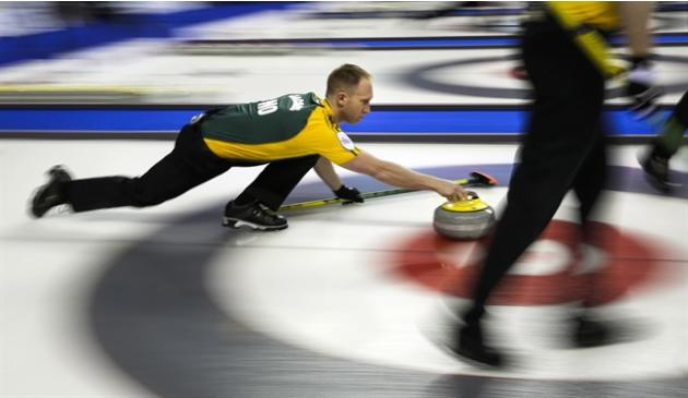 Northern Ontario skip Brad Jacobs, left, launches a rock as his team plays New Brunswick during curling action at the Brier in Calgary, Wednesday, March 4, 2015.THE CANADIAN PRESS/Jeff McIntosh