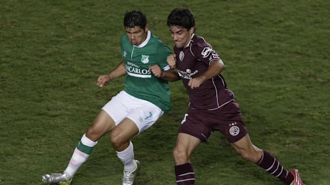 Robin Ramirez of Colombia's Deportivo Cali, left, fights for the ball with Carlos Araujo of Argentina's Lanus, during a Copa Libertadores soccer match in Cali, Colombia, Thursday, March 13, 2014