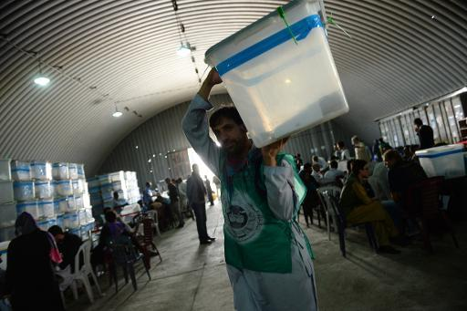 An election commission worker carries a ballot box during an audit of the presidential run-off vote in the country's general election at a counting centre in Kabul on August 25, 2014