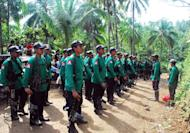In a file picture taken on December 26, 2009, members of the communist New People's Army (NPA) rebels stand in formation during the 41st founding anniversary of the Communist Party of the Philippines at an unspecified location in the southern Philippine island of Mindanao. Communist rebels recently attacked a major mining company in the central Philippines, killing five soldiers