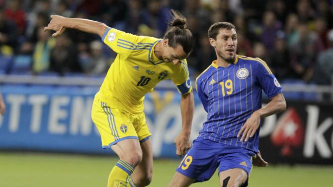 Kazakhstan's Anatoli Bogdanov fights for the ball with Sweden's Zlatan Ibrahimovic during their 2014 World Cup qualifying soccer match at the Astana Arena stadium in Astana
