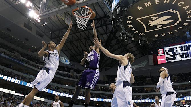 Dallas Mavericks' Brandan Wright, left, and Dirk Nowitzki, center right, of Germany defend as Sacramento Kings' James Johnson (52) goes up to score in the first half of an NBA basketball game Wednesday, Feb. 13, 2013, in Dallas. (AP Photo/Tony Gutierrez)