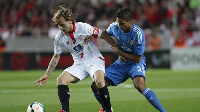 Real Madrid's Raphael Varane from France, right, and Sevilla's Ivan Rakitic from Croacia vie for the ball during their La Liga soccer match at the Ramon Sanchez Pizjuan stadium, in Seville, Spain on Wednesday, March 26, 2014