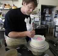 File - In this March 10, 2014 file photo, Masterpiece Cakeshop owner Jack Phillips decorates a cake inside his store, in Lakewood, Colo. Colorado's Civil Rights Commission on Friday upheld a judge's ruling that Phillips cannot refuse to make wedding cakes for same-sex couples, despite Phillips' cited religious opposition to same sex marriage. The panel says doing so violates state laws prohibiting businesses from discriminating against gay people. (AP Photo/Brennan Linsley, file)