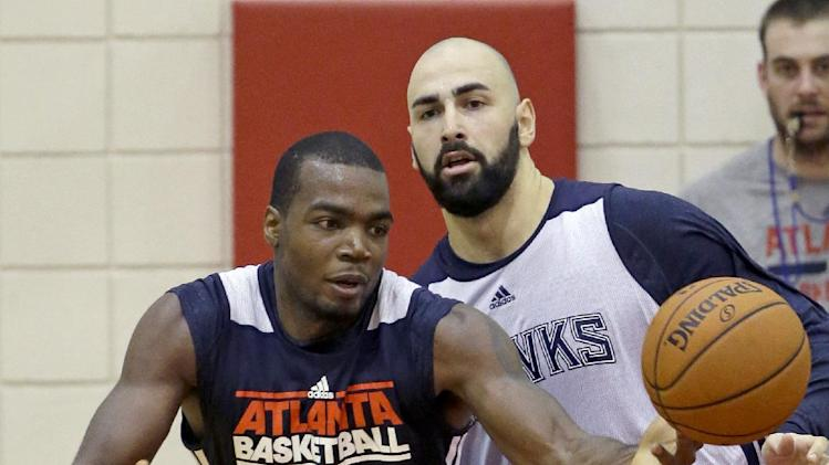 Atlanta Hawks' Paul Millsap, left, handles the ball against teammate Pero Antic, of Macedonia, during NBA basketball training camp, Tuesday, Oct. 1, 2013, in Athens, Ga