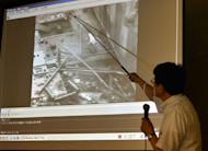 Masayuki Ono, acting head of Tokyo Electric Power Co (TEPCO) nuclear power and facilities section, points at an image showing steam rising from the unit 3 reactor building at the Fukushima Dai-ichi nuclear plant, at a news conference at the company's headquarters in Tokyo on July 18, 2013. TEPCO insisted Thursday there was no sign of spiking radiation at the crippled facility despite the steam