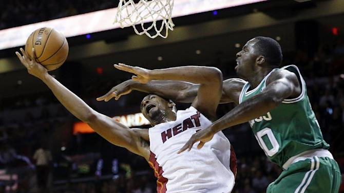 Miami Heat's Chris Bosh, left, attempts to shoot as Boston Celtics' Brandon Bass defends during the first half of an NBA basketball game Saturday, Nov. 9, 2013, in Miami