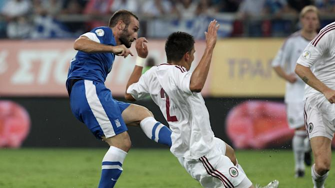 Greece's Dimitris Salpingidis, left, scores as Latvia's Vitalijs tries to stop him during their World Cup Group G qualifying soccer match at the Karaiskaki stadium in Piraeus port, near Athens, on Tuesday, Sept. 10, 2013. Greece won 1-0