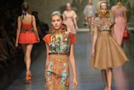 Models walk the runway at the Dolce & Gabbana show on September 23 during Milan fashion week. Models sashayed down the runway wearing satin, striped one-pieces in the candy pinks and blues, worn with foulard head-pieces and earrings
