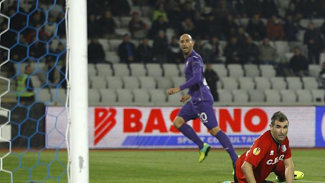 Fiorentina's Borja Valero, center, scores past Pandurii's goalkeeper Pedro Mingote, bottom, in the final moments of a Europa League, group E match, between Fiorentina and Pandurii, at the Cluj Arena stadium in Cluj, Romania, Thursday, Nov. 7,  2013