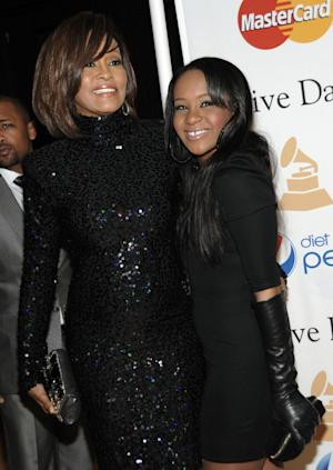 """FILE - In this Feb. 12, 2011 file photo, singer Whitney Houston, left, and her daughter Bobbi Kristina arrive at the Pre-Grammy Gala & Salute to Industry Icons with Clive Davis honoring David Geffen in Beverly Hills, Calif. Bobbi Kristina Brown has been spotted wearing a sparkly bauble on her ring finger, but she's not planning on getting married anytime soon. A rep for Brown's mother, the late Whitney Houston, says the 19-year-old is """"simply wearing her mother's ring"""" and that she's not engaged. (AP Photo/Dan Steinberg, file)"""