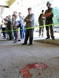 Blood stains the ground as Syrian security forces inspect the site of a blast in the central Midan district of Damascus
