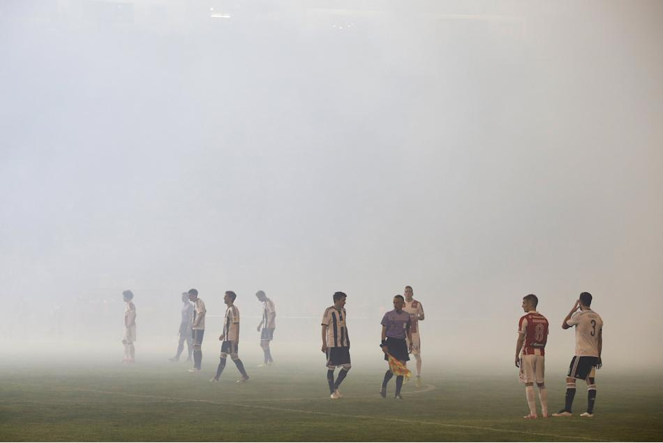 Red Star Belgrade and Partizan Belgrade players stand on the pitch amidst smoke during their Serbian Superliga soccer match in Belgrade