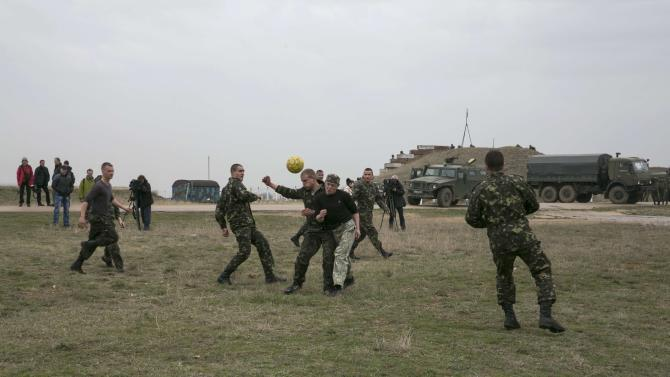 Ukrainian serviceman play soccer near Russian military vehicles at Belbek airport in the Crimea region