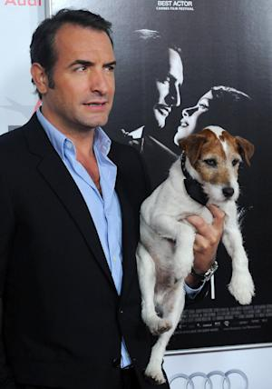 "FILE - In this Nov. 8, 2011 file photo, Jean Dujardin holds his co-star Uggie the dog arrive at the AFI gala screening of ""The Artist"" at Grauman's Chinese Theater in Los Angeles. Hollywood really has gone to the dogs this year. There's even a brand-new awards show, The Golden Collar Awards, honoring canine performers. Alan Siskind, creator of Dog News Daily, a website and marketing firm, came up with the idea to honor on-screen dogs in January when he noticed how many films prominently featured man's best friend.(AP Photo/Katy Winn, file)"
