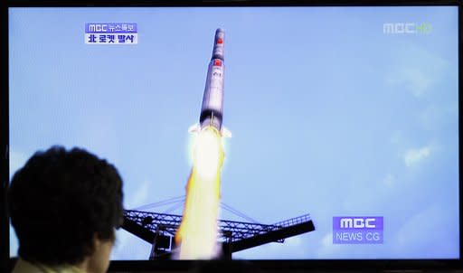 A South Korean woman watches a TV news report showing a computer generated image of North Korea's long-range rocket at Seoul train station in Seoul, South Korea, Friday, April 13, 2012. North Korea fi