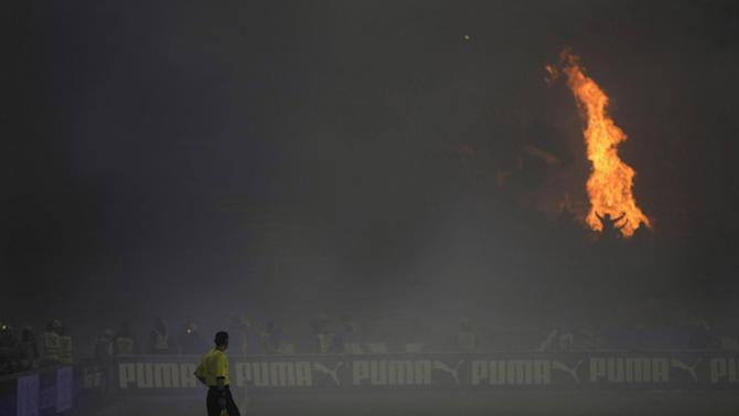 A soccer referee watches as Partizan Belgrade fans ignite a large fire on the stands during their team's Serbian league soccer game against arch rivals Red Star in Belgrade, Serbia, Saturday, Nov. 2, 2013. Marred with bouts of fan violence and frequent match fixing scandals, Serbian soccer seems to be in deep crisis, resulting with the national team failing to qualify for the 2014 World Cup