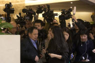 A relative of Chinese passengers aboard the missing Malaysia Airlines, MH370, left, is surrounded by journalists as he leaves after learning about the latest debris field found in a remote part of the Indian Ocean near Australia at a hotel in Beijing, China, Thursday, March 20, 2014. Four military search planes were dispatched Thursday to try to determine whether two large objects bobbing in a remote part of the Indian Ocean were part of a possible debris field of the missing Malaysia Airlines flight. (AP Photo/Ng Han Guan)