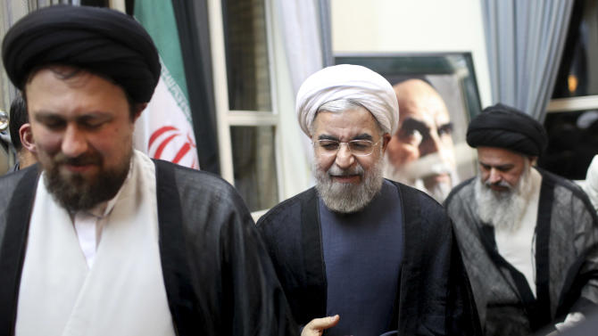 "Iranian President elect Hasan Rowhani, center, is accompanied by Hasan Khomeini, the grandson of the late revolutionary founder Ayatollah Khomeini, left, and Ayatollah Mousavi Bojnourdi, during visit of Ayatollah Khomeini's shrine, just outside Tehran, Iran, Sunday, June 16, 2013. Iran's newly elected reformist-backed president Hasan Rowhani said Sunday that the country's dire economic problems cannot be solved ""overnight,"" as he took his first steps in consulting with members of the clerically dominated establishment on his new policies. (AP Photo/Ebrahim Noroozi)"