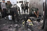 Indonesian police and soldiers clean up debris after a Christian school was set on fire in Temanggung town in Central Java province in 2011