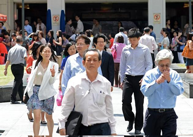 Pedestrians pictured in a downtown financial district of Singapore on January 29, 2013. Singapore has defended its population policies after an outcry over a forecast that it could have 30 percent more people in less than 20 years, with foreigners forming almost half the total