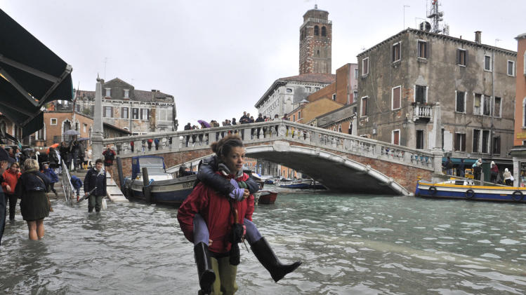 People walk in high water near the Ponte delle Guglie in Venice, Italy, Thursday, Nov. 1, 2012. High tides have flooded Venice, leading Venetians and tourists to don high boots and use wooden walkways to cross St. Mark's Square and other areas under water. Flooding is common this time of year and Thursday's level that reached a peak of 55 inches (140 centimeters) was below the 63 inches (160 centimeters) recorded four years ago in the worst flooding in decades. (AP Photo/Luigi Costantini)