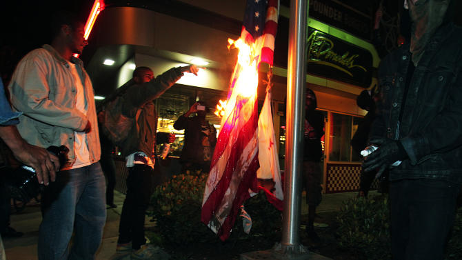 Marchers burn a United States flag outside a fast food restaurant during a protest after George Zimmerman was found not guilty in the 2012 shooting death of teenager Trayvon Martin, early Sunday, July 14, 2013, in Oakland, Calif. Protesters angered by the acquittal Zimmerman held largely peaceful demonstrations in three California cities, but broke windows and started small street fires Oakland, police said. (AP Photo/Bay Area News Group, Anda Chu)