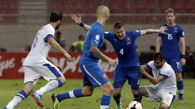 Greece's Giannis Maniatis, second right, tries to stop Slovakia's Jan Durica during their World Cup Group G qualifying soccer match at the Karaiskaki stadium in the port of Piraeus, near Athens, Friday, Oct. 11, 2013