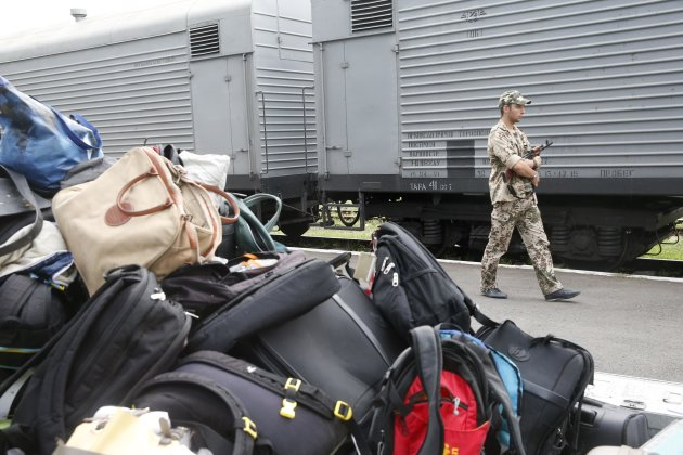 An armed pro-Russian separatist stands guard near the train transporting the remains of victims from the crashed Malaysia Airlines Boeing 777 plane before its departure, with bags and suitcases of passengers seen in the foreground, from the railway station in the eastern Ukrainian town of Torez, Donetsk region July 21, 2014. A train carrying victims from the site where Malaysia Airlines Flight MH17 crashed has set off from the rebel-held town of Torez in eastern Ukraine, a Reuters witness said on Monday. REUTERS/Maxim Zmeyev (UKRAINE - Tags: DISASTER POLITICS TRANSPORT)